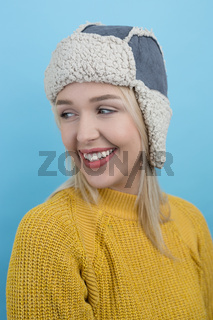 happy young woman in a woolly winter hat with earflaps against blue background