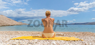 Rear view of sexy young caucasian woman sunbathing topless on romote pabble beach on Pag island, Croatia, Mediterranean.