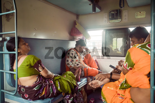 Patna India May 2019 - Tired exhausted woman Passengers falling asleep in a long ride, sitting in their seat and taking a nap inside a train compartment while traveling in public rail transportation