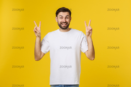 Young handsome man wearing striped t-shirt over isolated yellow background smiling looking to the camera showing fingers doing victory sign. Number two