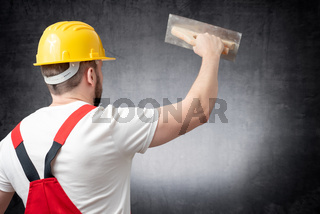 Rear view of a worker plastering a wall indoors