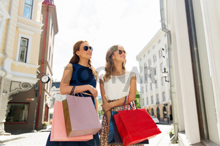 happy women with shopping bags at storefront
