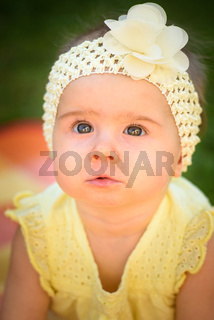 portrait of cute baby girl in yellow band and dress sits in sunny backyard. 8 months old infant outdoors