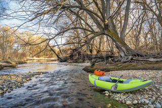 whitewater inflatable kayak on a river shore