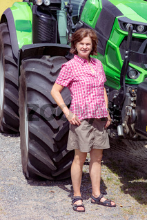 Farmer is standing next to her tractor