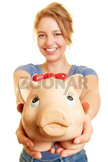 Junge Frau hält Sparbüchse oder Sparschwein