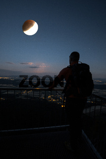 Man on the top of the mountain looking at full moon