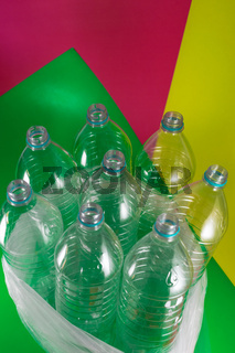 A pack of 8 empty and recyclable plastic water bottles, with no caps, blue seal, in a plastic bag, on a geometrical colored vibrant sea green, wine red, and yellow background. Reuse, Eco-Friendly, Environment concept.