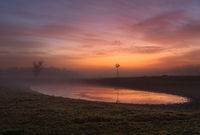 Red skies at dawn with light mist across rural farmlands