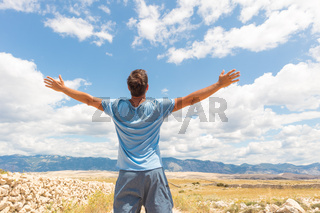Rear view of casual sporty man standing on a dirt country road rising hands up to the clouds on a blue summer sky. Freedom and travel adventure concept.