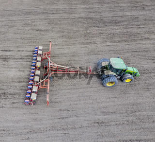 Sowing of corn. Tractor with a seeder on the field. Using a seeder for planting corn.