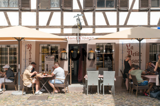 people enjoying a meal in French cafe in the old city center of Strasbourg