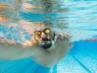 Young male athlete swimming freestyle crawl under water view