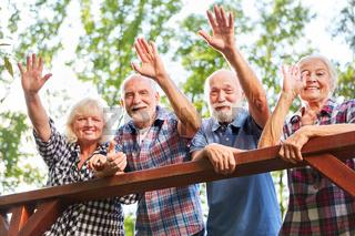 Fröhliche Senioren winken von einer Brücke
