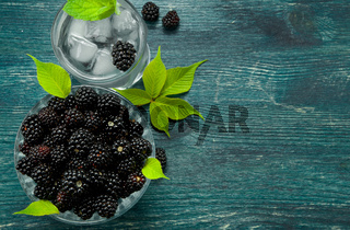 Fresh blackberry. Juicy blackberry in a bowl and a glass of cold ice water with berries on a wooden table. View from above. Copy space.