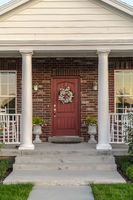 Front door to a house flanked by two pillars