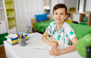 happy boy writing or drawing to notebook at home
