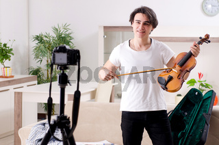 Young male blogger playing violin at home