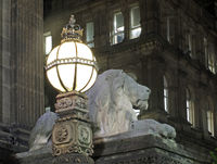 old street light and lion sculpture on the 19th century leeds city hall building at night with the historic library building in the background
