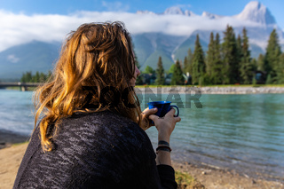 Lady drinks her coffee on Canmore BC riverside