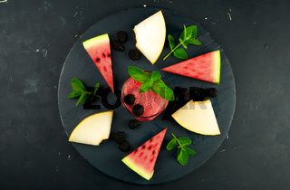 MELON WATERMELON BLACKBERRIES MINT AND A GLASS OF JUICE ON ROUND WOODEN BACKGROUND. RIPE WATERMELON JUICY MELON BLACKBERRY MINT COCKTAILS ON A DARK WOODEN BOARD ON A DARK BACKGROUND.