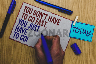 Conceptual hand writing showing You Don t not Have To Go Fast, You Just Have To Go. Business photo text just start to reach Man holding marker paper clothespin express ideas wooden table.