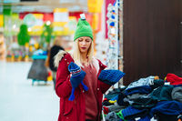 Young woman choosing hat in shopping center
