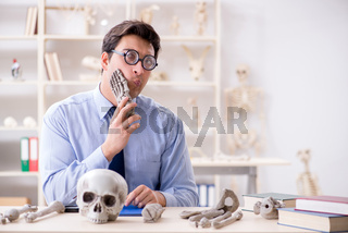 Funny crazy professor studying human skeleton