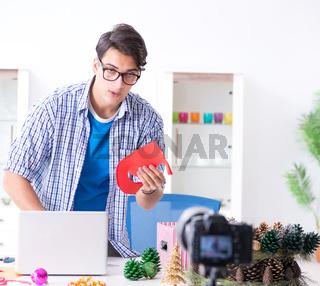 Video blogger recording making paper decoration