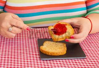 A woman with painted nails smearing red raspberry jam with a knife on a slice of toast