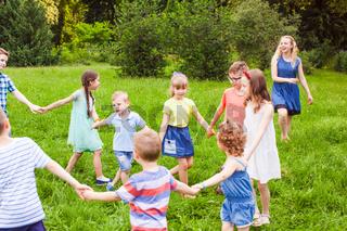 Joyful kids dancing holding hands in summer park.