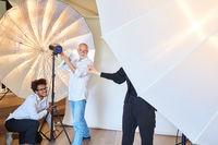 Fotografen Team bereitet Blitzlicht für Fotoshooting vor