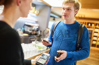 Junger Mann bezahlt mit Smartphone via NFC