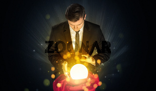 Businessman  sitting with sparkling magic ball