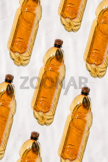 Bottles of brown color lie on a white background in a row. The bright sun shines on colored plastic, creating a shadow from the bottle. Production of plastic bottles. Minimalism design