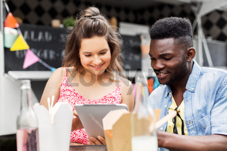 mixed race couple with tablet pc at food truck