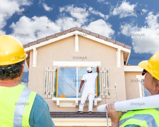 Male and Female Contractors Overlooking Painter Painting House