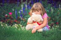 Adorable girl hugging her teddy bear in summer park