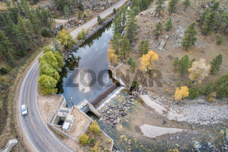 river with a dam in mountain canyon aerial view