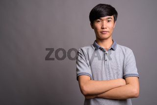 Young Asian man wearing gray polo shirt against gray background