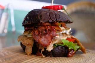 Side view of Big messy burger served on chopping board