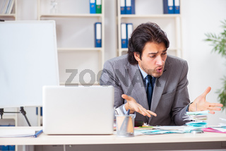 Young handsome businessman in budget planning concept
