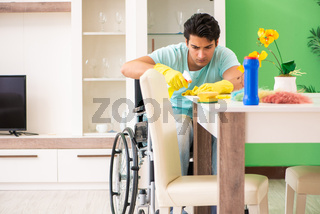 Disabled man on wheelchair cleaning house